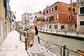 Italy wedding in Venice. Newlyweds stand embracing on the banks of the Venice Canal. The groom hugs the bride by the waist. White wedding dress with small beautiful train and sand-colored men's suit.