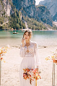 Beautiful bride in a white dress with sleeves and lace, with a yellow autumn bouquet on background of the arch for ceremony, at Lago di Braies in Italy. Destination wedding in Europe, on Braies lake.