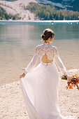 Beautiful bride in a white dress with sleeves and lace, with a yellow autumn bouquet of dried flowers and peony roses, on the Lago di Braies in Italy. Destination wedding in Europe, on Braies lake.