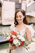 Venice wedding in Italy. A bride in a white dress, with a train, with a bouquet of white and red roses in her hands, stands on the pier near the moored gondola in a narrow Venetian canal.