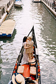 Italy wedding in Venice. A gondolier rolls a bride and groom in a classic wooden gondola along a narrow Venetian canal. Newlyweds are standing in the boat, rear view.