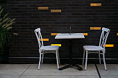 A table and white chairs set up for two people under social distancing rules during the covid-19 pandemic at a sidewalk cafe