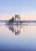 Scenic nature landscape with mood fog and beautiful sunrise at early summer morning in lakeside Finland