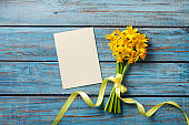 Spring daffodil flowers and clean card on rustic background. Beautiful bouquet for Women day or Mother day top view.