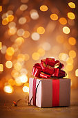 Christmas or Birthday gift box with red ribbon against golden lights bokeh background. Vertical holiday greeting card.