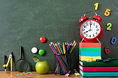Back to school or education concept with alarm clock, green apple and school supplies against blackboard on wooden table.