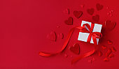 Red Valentines day background. Gift box and mixed hearts top view. Flat lay.