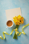 Morning cup of coffee, clean card and spring daffodil flowers on blue table. Beautiful breakfast for Woman day, Mother day. Top view.