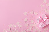 Gift box and confetti hearts. Pink pastel color. Flat lay. Valentines day concept.