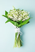 lily of the valley flowers bouquet on pastel blue background. flat lay. top view. wedding background. vertical orientation