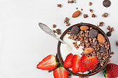 bowl of oat chocolate granola with yogurt, fresh strawberries and nuts with a spoon on white marble background