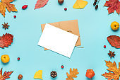 Thanksgiving autumn greeting card or invitation. Dried leaves, flowers, nuts, berries on blue background. Flat lay, mock up