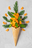 mandarin orange fruits in waffle ice cream cone with slices and fir tree branches. Christmas food concept. top view. flat lay