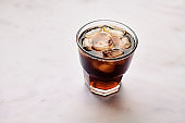 Glass of Iced black coffee against a marble backdrop.