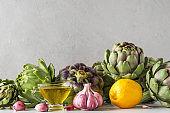 Healthy vegan food concept. Fresh ripe artichokes with olive oil, lemon and garlic on concrete background. Italian cuisine