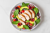 Salad with grilled chicken breast, avocado, spinach, cherry berries and tomato on white background. healthy diet food