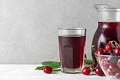 Cherry juice in a glass and jug with fresh berries on white background. Refreshment summer drink