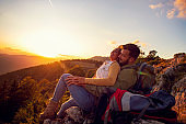 Couple Man and Woman sitting on cliff enjoying mountains and clouds landscape Love and Travel happy emotions Lifestyle concept.