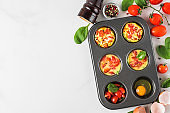 Baked egg muffin cups with spinach and tomatoes in muffin tin. Cooking concept. Healthy keto diet breakfast. top view