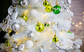 Sweet toys of green shades hang on white Christmas tree