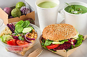 Healthy vegan food delivery. Packed burger, buddha bowl salad, green soup, energy balls and matcha latte in boxes and cups