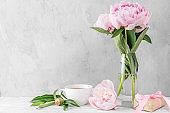 Still life with pink pastel peony flowers, gift box and coffee cup on white table. spring holiday or wedding concept