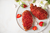 Croissants with berry jam and fresh strawberries in a plate and blossom flowers on white marble background. top view