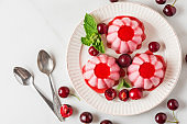 Panna cotta dessert with fresh cherries, syrup and mint in a plate with spoons. Healthy italian vegan food. top view