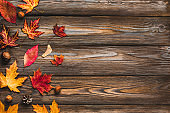 Autumn composition made of autumn leaves, flowers, nuts, pine cones on rustic wooden background. Flat lay, top view