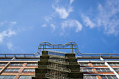 Old Office building exterior with fire escape staircase and clear blue sky