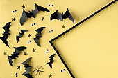 Halloween frame template with black paper bats and plastic spooky eyes on a yellow background.