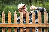 Senior man painting wooden fence in garden