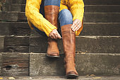 Woman fasten zipper on her leather boot