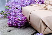 Handmade gift boxes wrapped with craft brown paper, decorated with fresh purple lilac flowers on a vintage wooden surface.