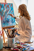 Talented young woman is painting on canvas at easel in art school