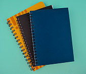 Some different colored paper diaries isolated on a light blue isolated paper background