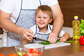 A happy father and a young son prepare a salad in the kitchen with vegetables. My dad teaches me how to cut tomatoes on a blackboard. Concept of diet food