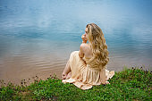 Beautiful sad girl sitting on the shore of the lake in a dress , the concept of loneliness