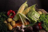 Dark moody still life of fresh vegetables on a wooden table. Healthy organic local food.