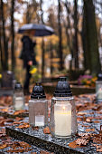 Candle lantern at grave. Mourning woman in defocused graveyard