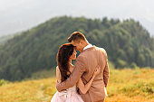 The bride and groom are standing with their backs and hugging. Sunset. Wedding photo on a background of autumn mountains. A strong wind inflates hair and dress.