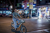Blurred cyclist woman at the night streets of Hanoi