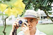 Senior Asian man photographig flower