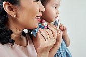 Mom and daughter applying lipstick