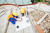 Civil engineers pointing at building plan