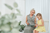 Mother showing book to daughter