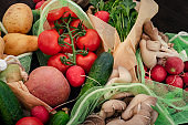 Vegetable in reusable bags on wood background, top view