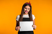 Pretty asian girl holding white a4 paper poster. Copy space. Smiling trendy woman with long hair on studio background.