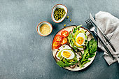 Avocado toasts with cottage cheese, eggs, arugula on dark table. Healthy breakfast, snack. Top view