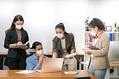 Asian office workers wearing face masks working in the new normal office and doing social distancing during coronavirus COVID-19 pandemic